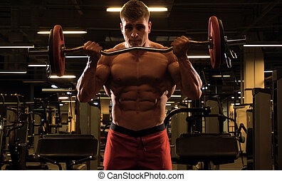 Man bodybuilder doing biceps exercise with barbell