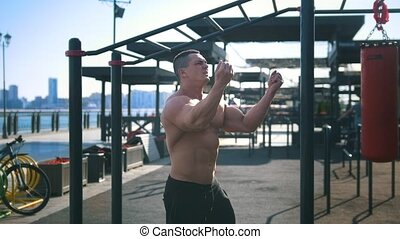 Man bodybuilder doing exercises for warm-up outdoor before...