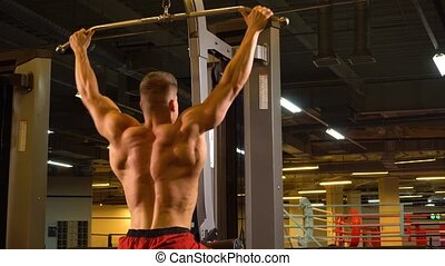 Man bodybuilder doing pulling on back in the gym