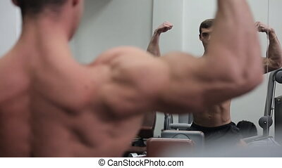 Man bodybuilder in front of the mirror getting ready for a competition