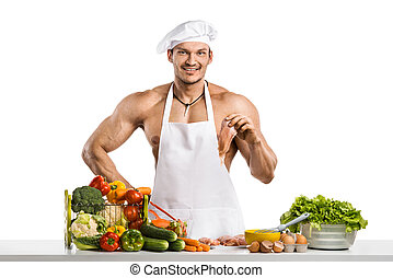 Man bodybuilder in white toque blanche and cook protective apron, concoction vegetables and fruit, on whie background, isolated