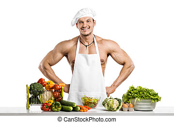 Man bodybuilder in white toque blanche and cook protective apron, concoction vegetables and smile, on whie background, isolated