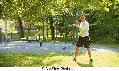 Man bodybuilder perform the warm-up before basic exercises -...