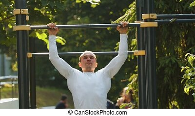 Man bodybuilder performs pull-ups on the bar - Mid shot