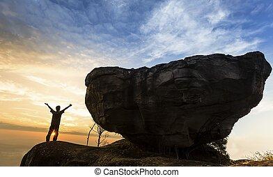 man, bovenop, berg, met, groot, rots