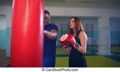man boxer coach teaches girl boxing at the gym