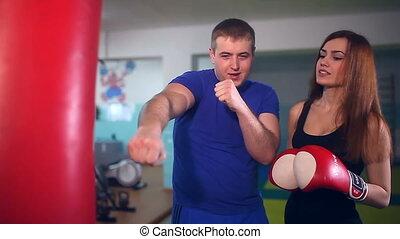 man boxer coach teaches girl boxing at sport gym