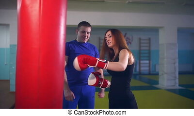 man boxer coach teaches girl boxing at gym