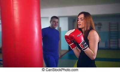 man boxer coach teaches girl sport boxing at gym