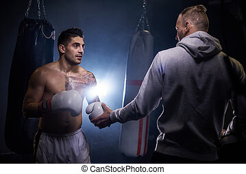 Man boxing with personal trainer