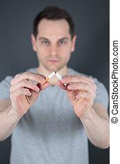 man breaking a cigarette stick