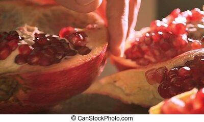 Man breaking a half of pomegranate