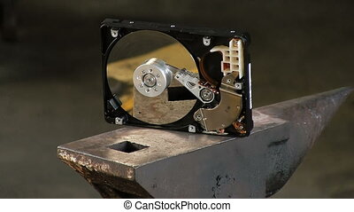 Man breaks the hard drive with a sledge heavy hammer, on the anvil. Slow motion Close-up have sound