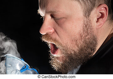 Man breathing through nebulizer mask