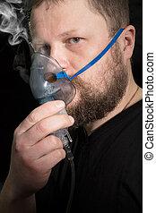 Man breathing through nebulizer mask