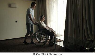 Man bring senior woman in a wheelchair at the room