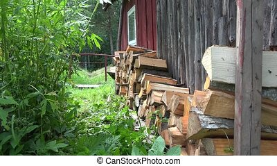man bring with wheelbarrow  wood and unload on home wall.