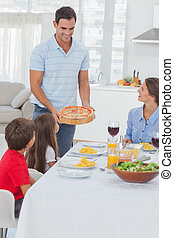 Man bringing a pizza to his family