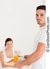 Man bringing breakfast looking at the camera