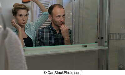 Man brushing teeth and woman combing hair in bathroom. Male carefully cares for teeth while his sweet wife combs chevelure with massage brush.