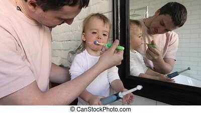 Man brushing teeth of adorable baby - Happy father helping...