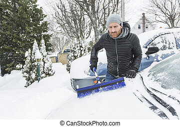 man brushing the snow off the windshield of his car