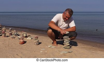 Man build stone pyramid on the beach
