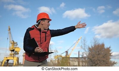 man builder construction worker in an orange helmet waving calling runs behind  crane and blue sky