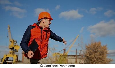man builder construction worker in an orange helmet waving calling runs behind the crane and blue sky