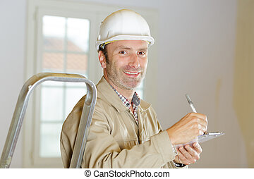 man builder in hard hat looking at camera