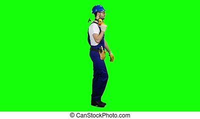Man builder with a hammer in his hands goes to the construction site. Green screen. Side view