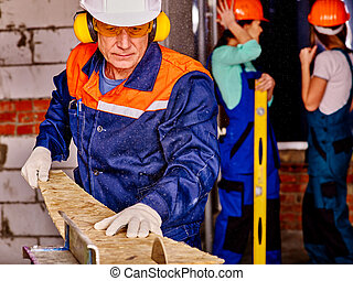 Man builder with circular saw . - Old man in blue builder...