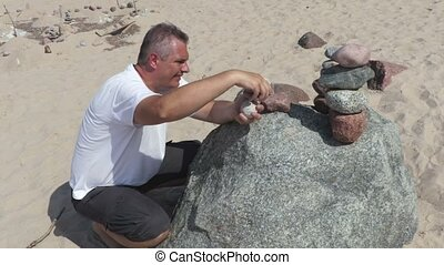 Man builds a balanced stone pyramid on the beach in summer day