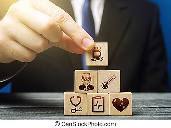 Man builds a block pyramid with medical icons symbols. Healthcare and medical Insurance. Supplies, equipment and specialists for the normal functioning of hospitals in the fight against the pandemic.