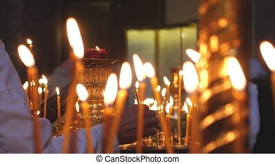 Man Burnes candles in the Church of Saint Petersburg....