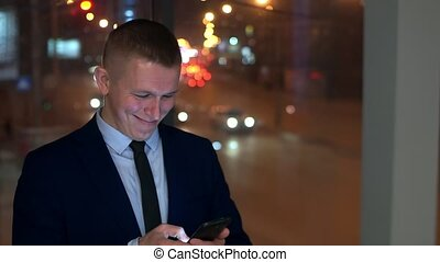 Man-businessman reading good news in the smartphone, smiling, near the window with the night city. Slow motion.