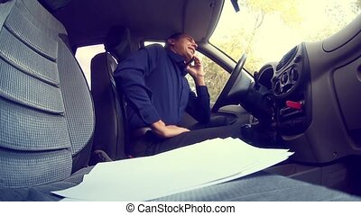 man businessman talking on the phone in car keeps documents...