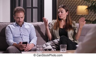 Close-up of conflicting couple wasting time on appointment with psychologist. Disinterested husband browsing on cellphone while wife explaining family problems to consultant, relationship difficulties
