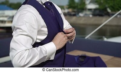 Man buttoning blue jacket on a yacht