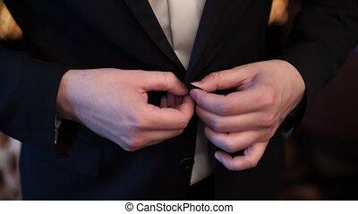 Man buttoning jacket closeup shot