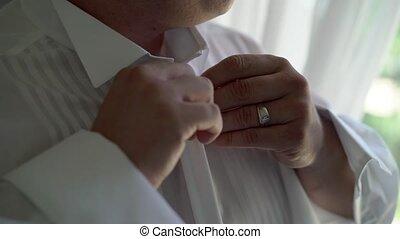Man buttoning shirt - Man buttoning white shirt closeup