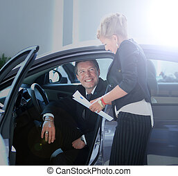 Man buying a car in dealership sitting in his new auto