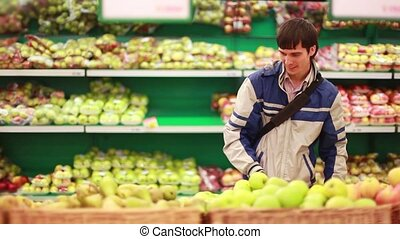 Man buying an apple in a supermarket. 1920x1080