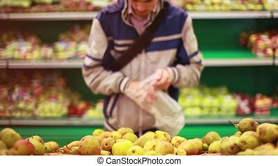 Man buying an apple in a supermarket. hd