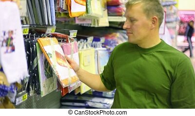 man buying bedding in supermarket