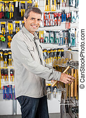 Man Buying Hammer In Hardware Store