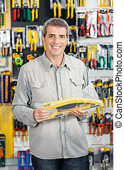 Man Buying Handsaw In Hardware Store