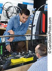 man buying parts in bike shop