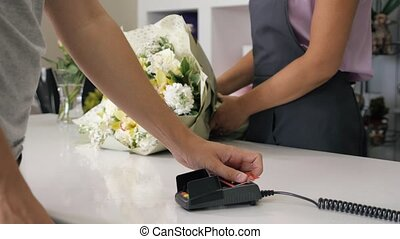 Woman seller florist gives a huge beautiful bunch of flowers to customer. Man buys bouquet in flower shop paying by card in payment terminal, hands closeup. Work day in floristry studio.