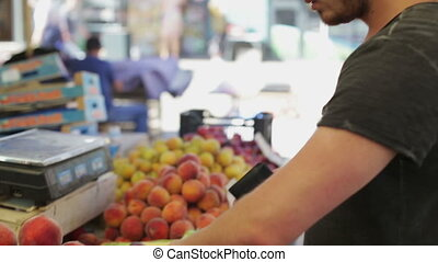 Man buys peaches at a vegetable market in the day